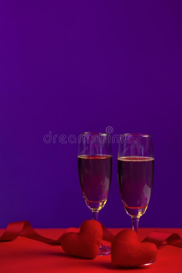 Champagne in glasses of two in romantic valentine concept with heart shaped fabric on red and purple background royalty free stock photography