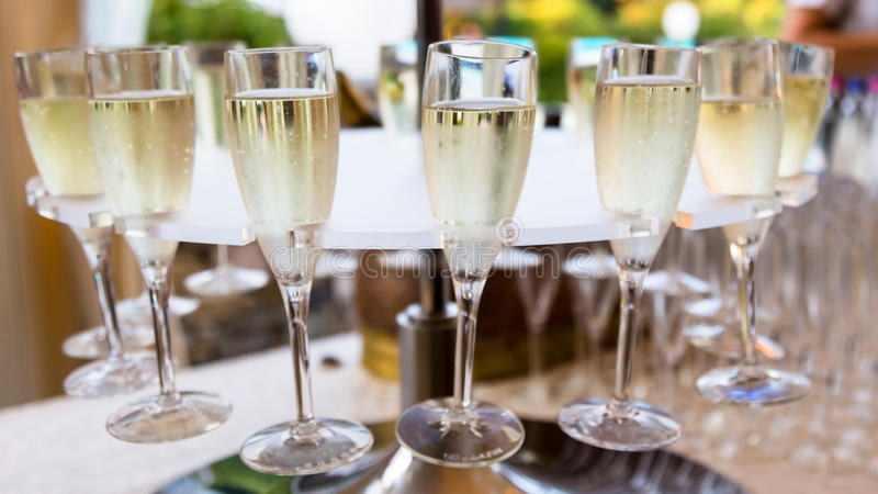 Champagne and glasses. Waiter pouring champagne on glass stock photo