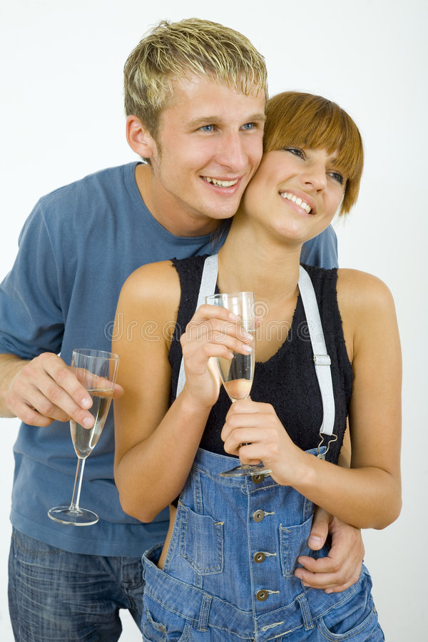 Champagne and hug. Young, smiling and hugging couple, celebrating removal with champagne. They're looking happy. Gray background stock images