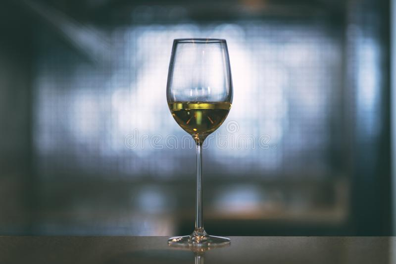 Champagne i ett vinexponeringsglas med suddig ljus bakgrund royaltyfri fotografi