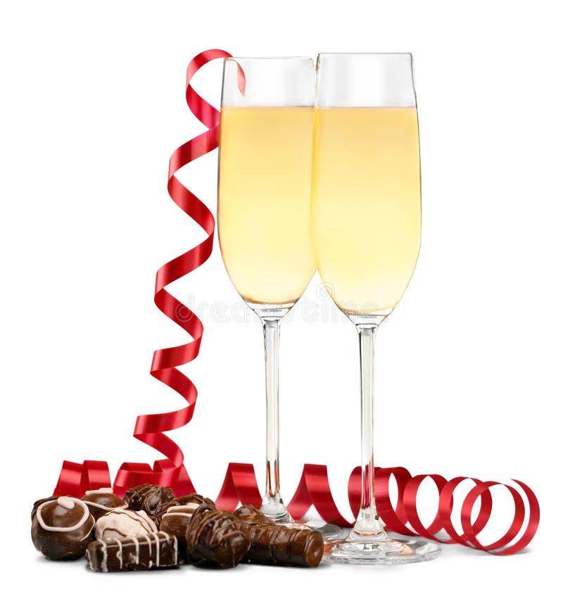Champagne nos vidros, na fita vermelha e no chocolate imagens de stock royalty free