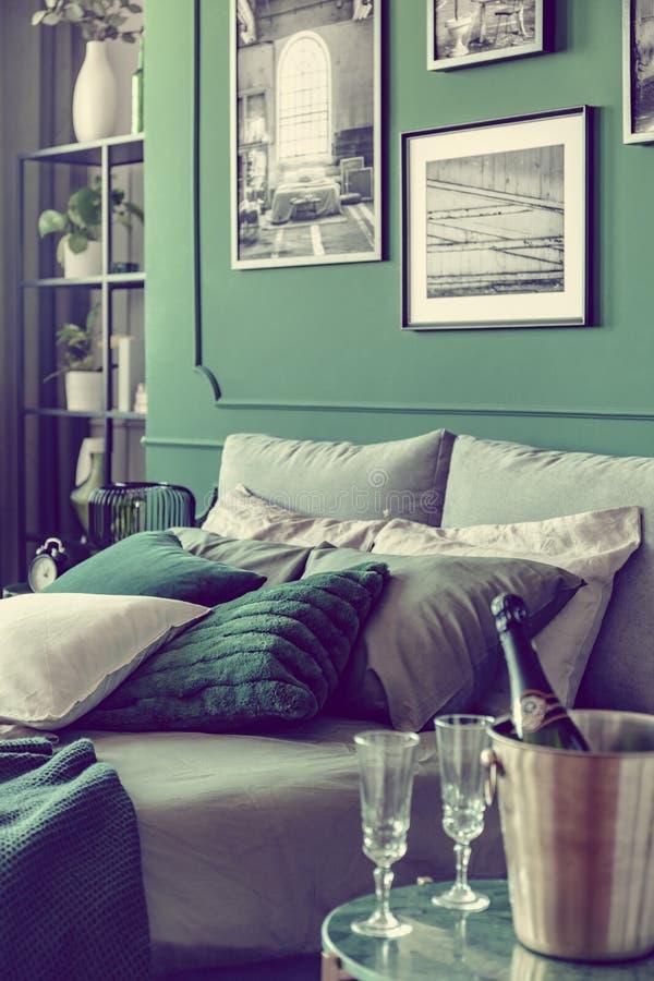 Champagne och exponeringsglas på nightstandtabellen bredvid konungformatsäng med lyxig sängkläder i elegant hotellrum royaltyfri fotografi