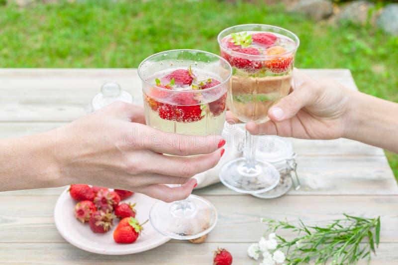 Champagne och jordgubbar Händer rymmer ett exponeringsglas med champagne och jordgubbar Sommarmatsammansättning på en trätabell arkivfoton