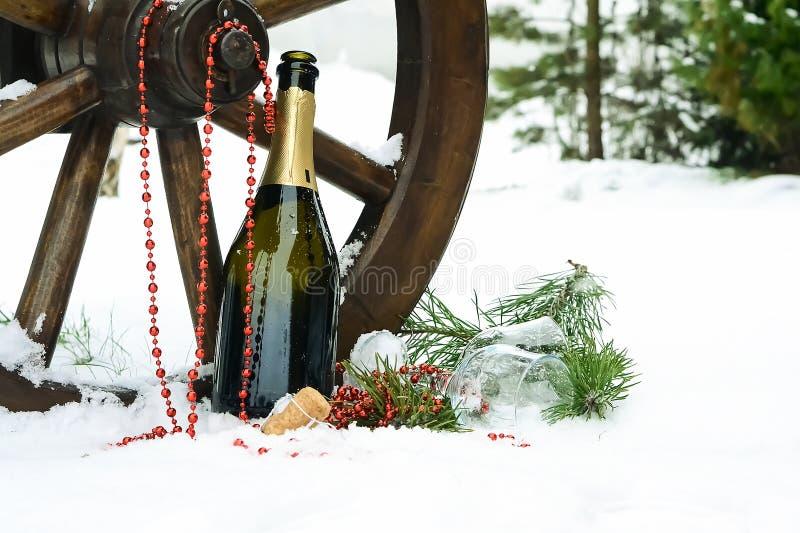 Champagne och julpynt i snön Feriedecorat arkivfoton