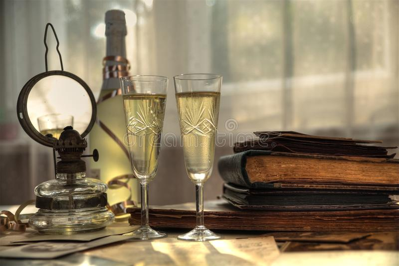 Champagne and old books. Chjampagne in glasses, bottle old photos and oil-lamp stock image