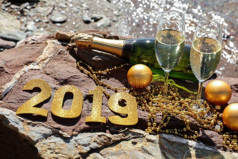 Champagne op een steenachtig strand door het overzees, Nieuwjaar viert voorbereidingsconcept royalty-vrije stock fotografie