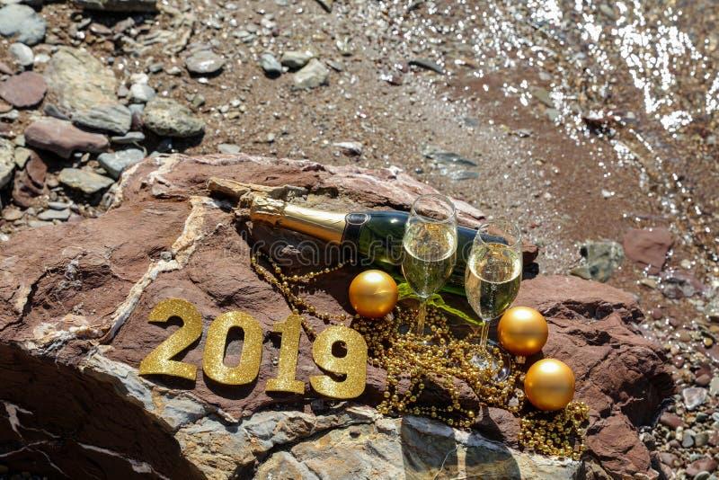 Champagne op een steenachtig strand door het overzees, Nieuwjaar viert voorbereidingsconcept stock fotografie