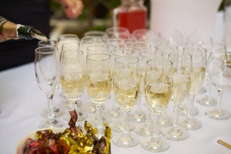 Champagne ou vin se renversant de barman dans des verres de vin sur la table à la cérémonie l'épousant solennelle d'extérieur image libre de droits