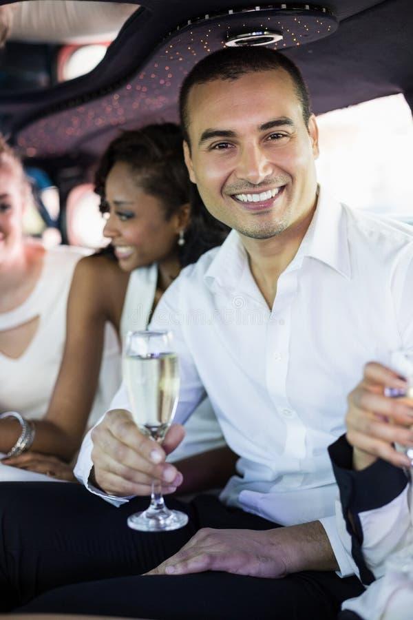 Champagne potable bien préparé d'homme dans une limousine photographie stock