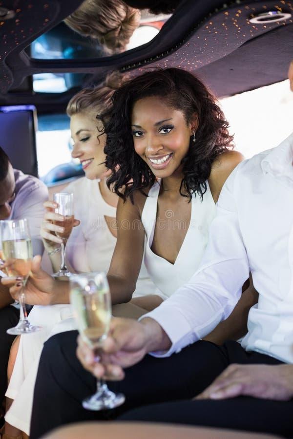 Champagne potable bien préparé de femme dans une limousine image libre de droits
