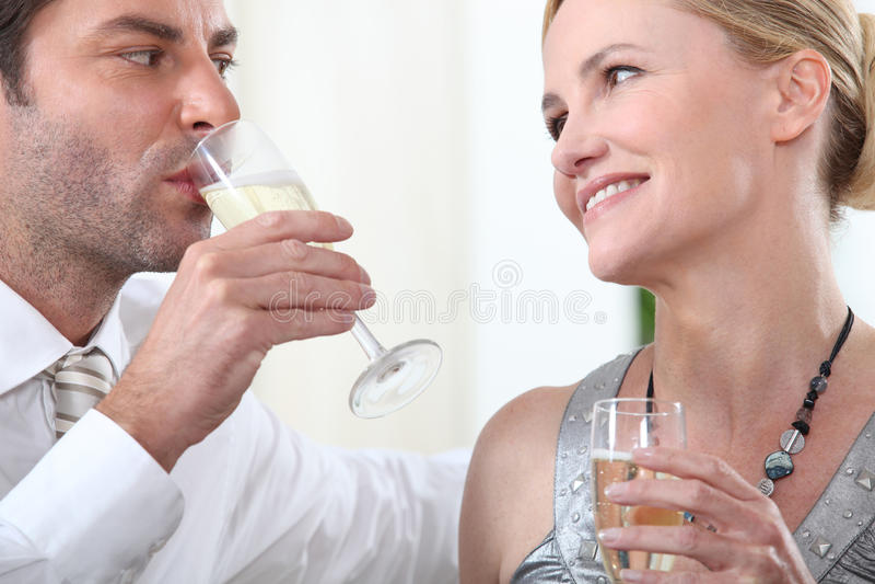 Champagne potable de couples photo stock