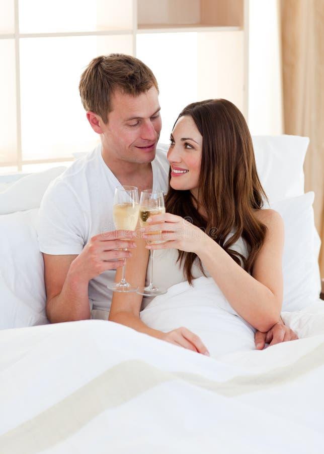 Champagne potable de couples intimes se situant dans le bâti photo stock