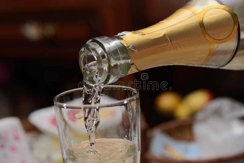Champagne is poured in a glass, close up royalty free stock image