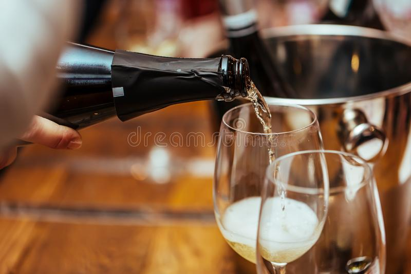 Champagne is poured into a glass standing on the table. royalty free stock photography