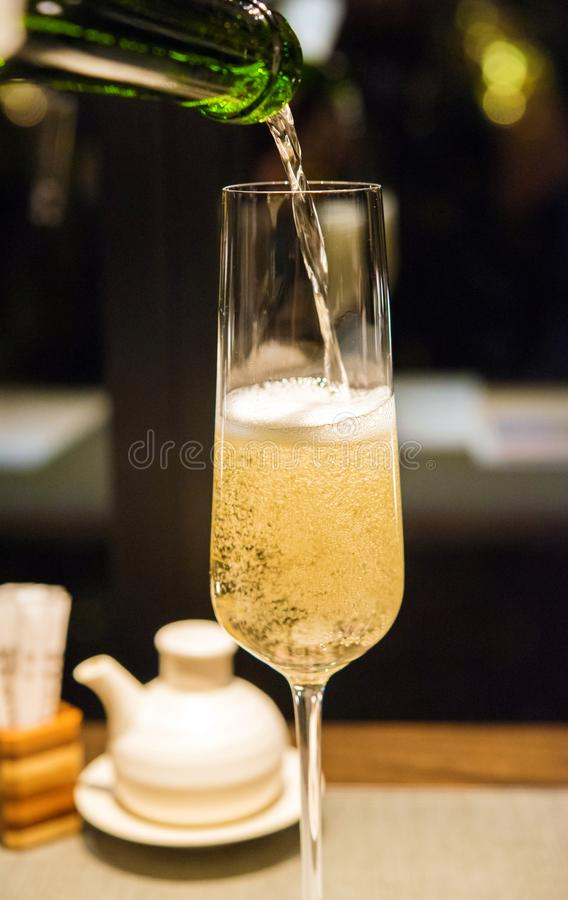 Champagne is poured into a glass, Tokyo, Japan. Vertical. Close-up. stock photos
