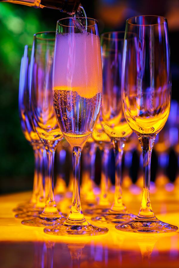 Champagne is poured into glasses. Highlighted in yellow and purple stock images