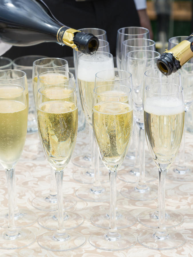 Champagne is poured into glasses. Unrecognizable waiter pours champagne dark glass bottles in tall glasses stock photos