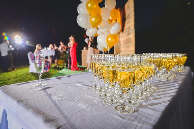 Champagne is poured into wine glasses. glasses of champagne stock images