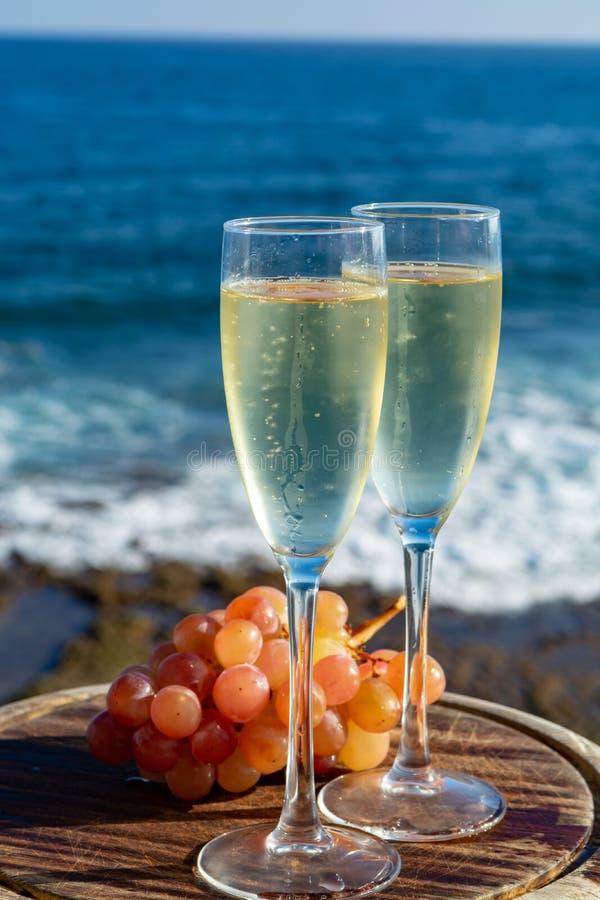 Champagne, prosecco ou cave servis avec du raisin rose en deux verres sur la terrasse extérieure avec la vue de mer photographie stock