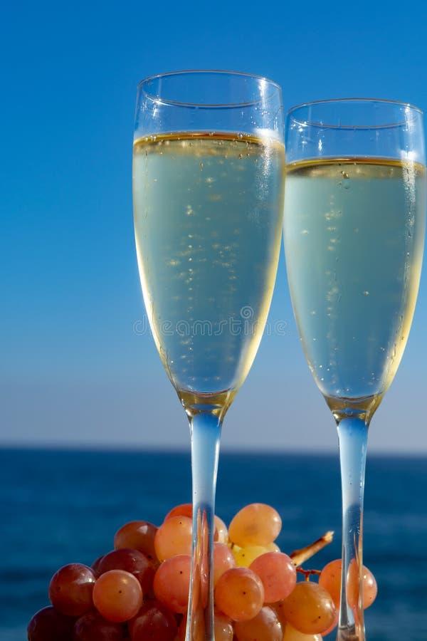 Champagne, prosecco ou cave servis avec du raisin rose en deux verres sur la terrasse extérieure avec la vue de mer image libre de droits
