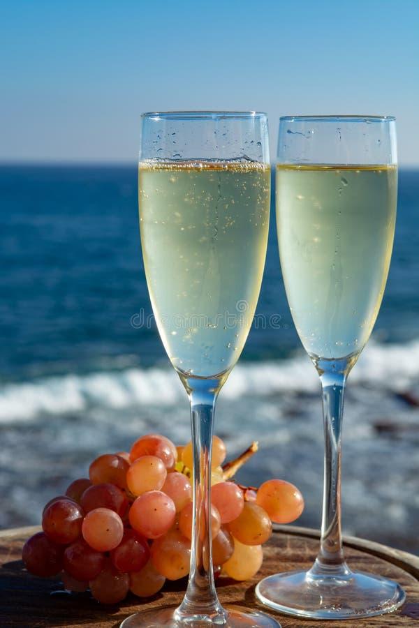 Champagne, prosecco ou cave servis avec du raisin rose en deux verres sur la terrasse extérieure avec la vue de mer photographie stock libre de droits