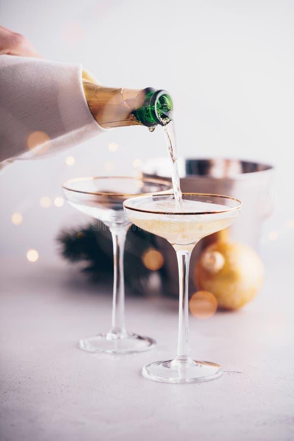 Champagne que derrama em vidros e em decorações do Natal fotografia de stock