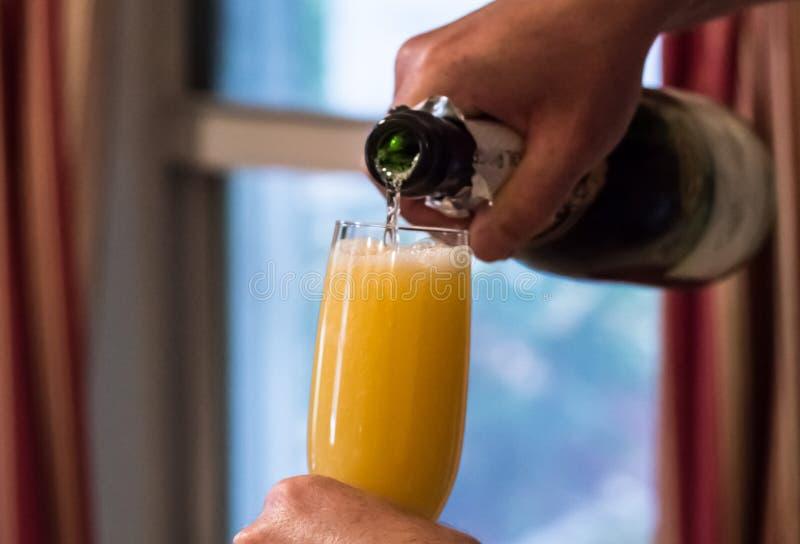 Champagne que está sendo derramado no vidro do suco de laranja fotografia de stock