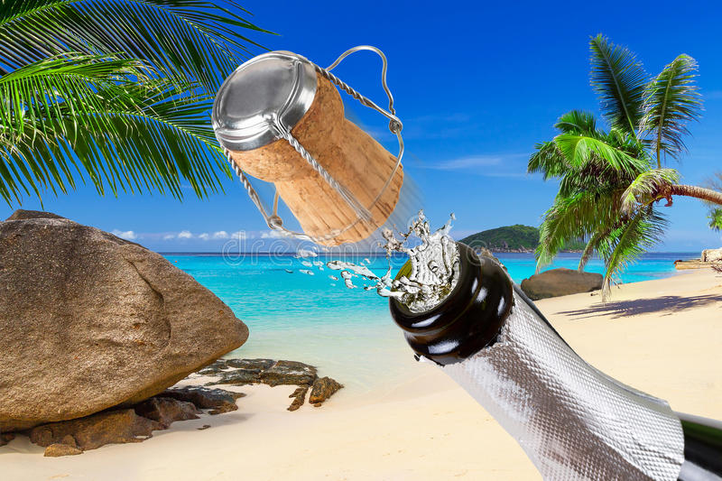 Champagne with splashes on the tropical beach royalty free stock image