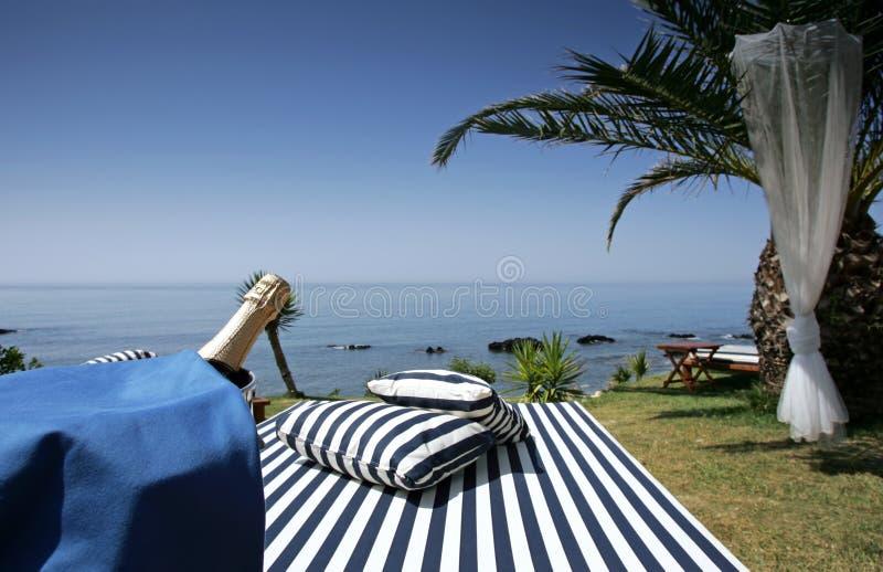 Champagne sunlounger und sonnige Seeansichten stockbild