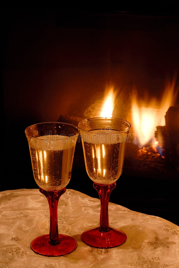 Champagne Toast. Two glasses of bubbly champagne wine in front of a fireplace for toasting a celebration royalty free stock photos