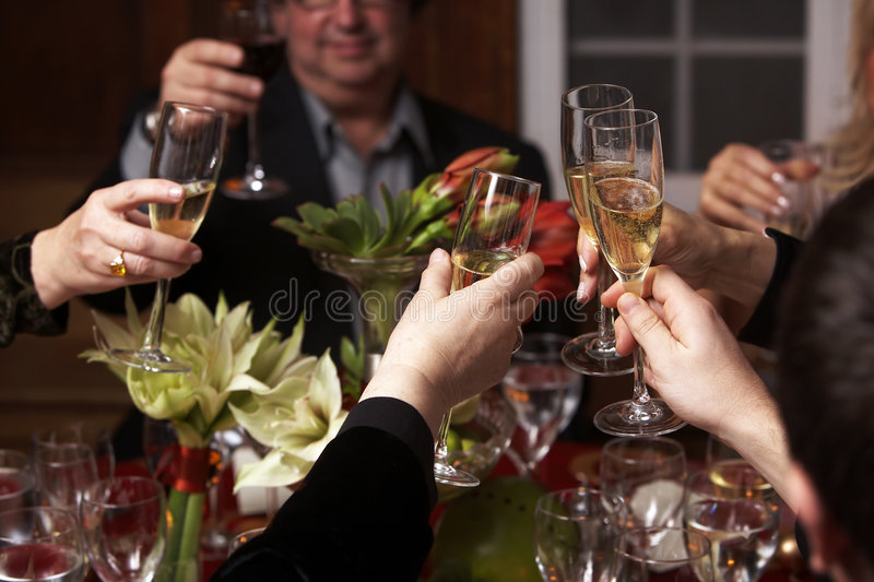 Champagne toast. Champagne glasses raised in a toast to the bride and groom royalty free stock photos