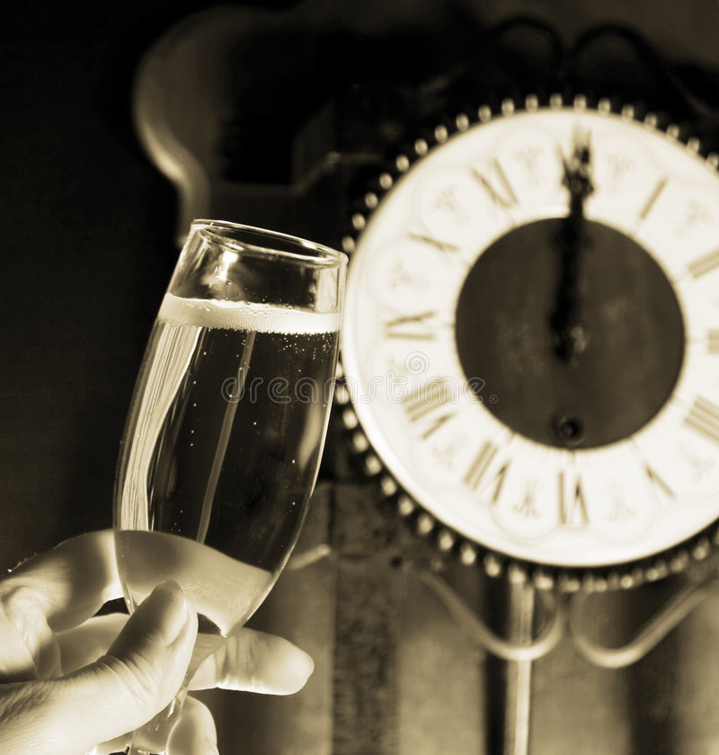 Champagne toast. At midnight with clock in the background royalty free stock image