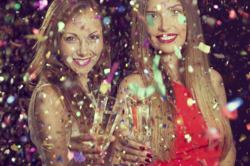 Champagne toast. Two beautiful young women having fun at a party, holding glasses of champagne and making a toast stock photo