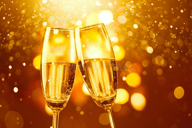 Champagne toast. Two glasses of champagne toasting against gold bokeh background