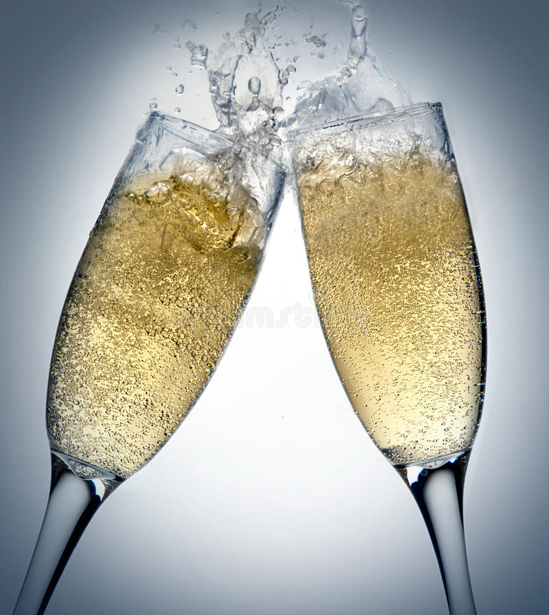 Champagne toasting. Two champagne glasses toasting splashing royalty free stock photos