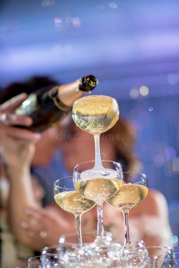 Champagne-toren met paar in huwelijkspartij stock fotografie