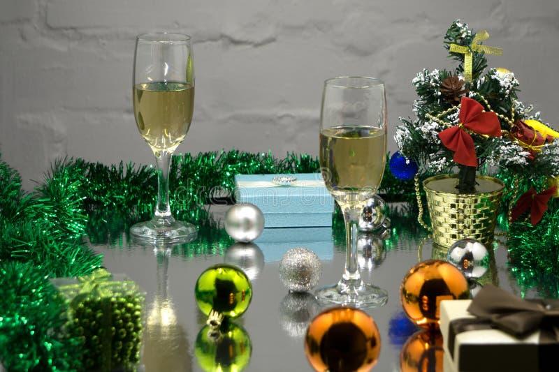 Champagneexponeringsglas, julgran-, julgåvor och julbollar på svart bakgrund royaltyfria bilder