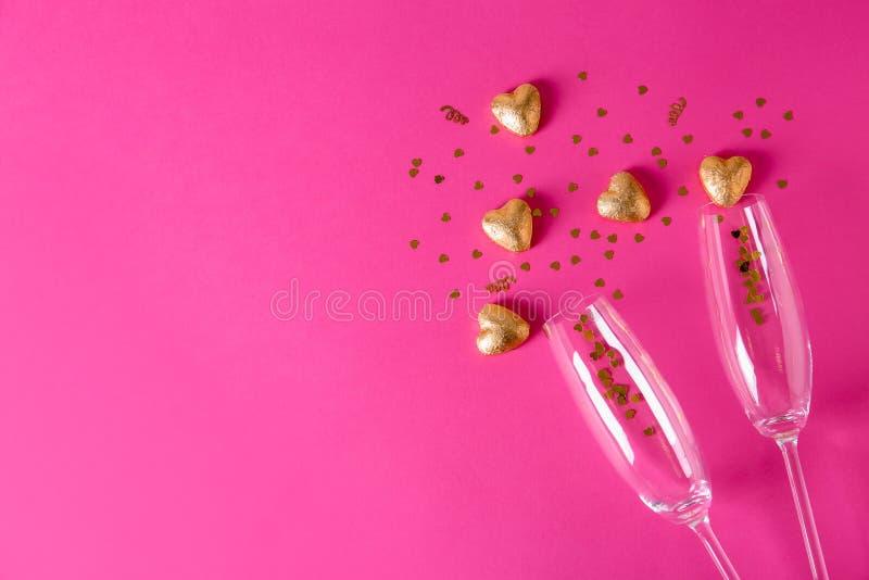 Champagneexponeringsglas och hjärta formade godisar i guld- folie på färgbakgrund arkivfoto