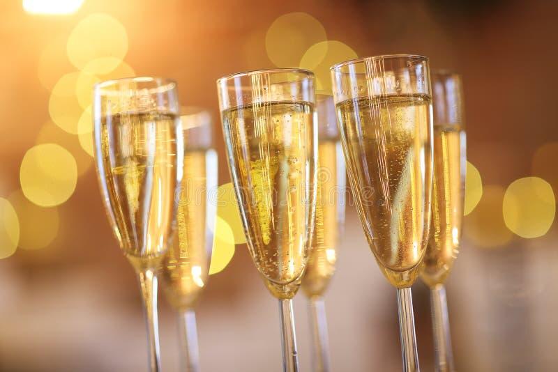 Champagneexponeringsglas på guld- bakgrund arkivfoton