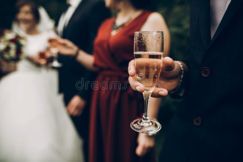 Champagneexponeringsglas på toastinen för bröllopmottagande, brud- och brudgum arkivbild