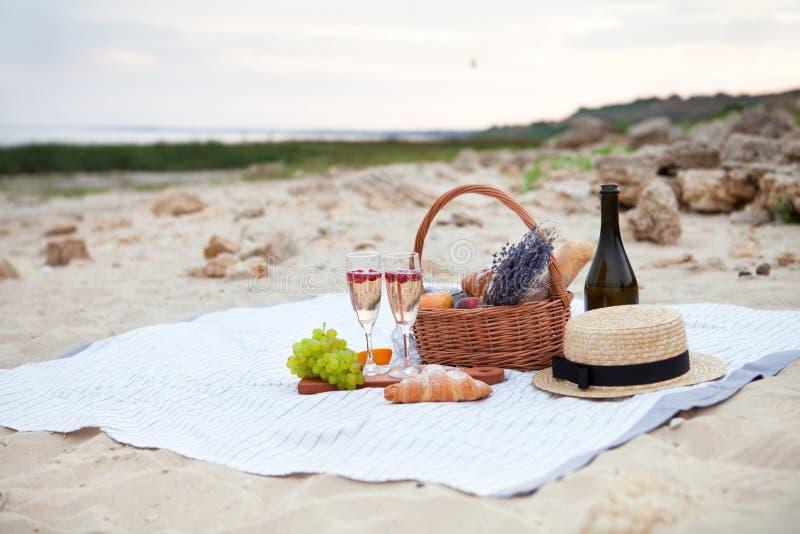 champagneexponeringsglas två Ha picknick på stranden på solnedgången i wen royaltyfri foto