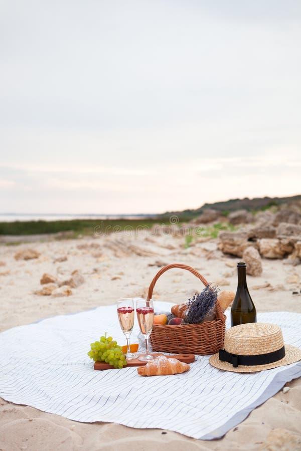 champagneexponeringsglas två Ha picknick på stranden på solnedgången i wen royaltyfri fotografi