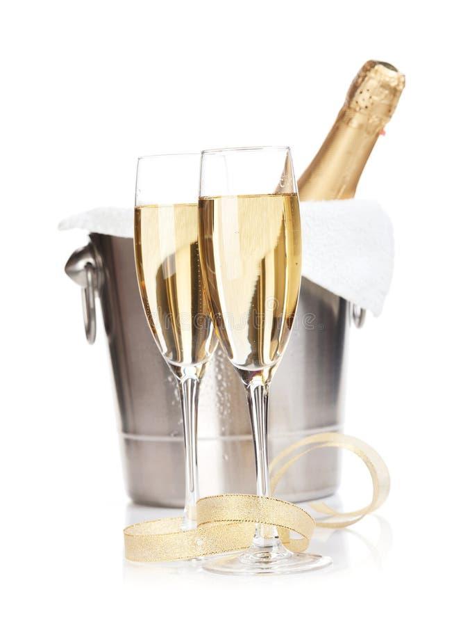 Champagneflaska i ishink, två exponeringsglas och juldekor royaltyfria bilder