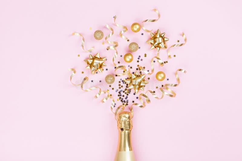 Champagneflaska med julgarnering från konfettistjärnor, guld- bollar och partibanderoller på rosa bakgrund Lekmanna- lägenhet arkivfoton