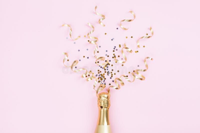 Champagneflaska med konfettistjärnor och partibanderoller på rosa bakgrund Jul, födelsedag eller bröllopbegrepp Lekmanna- lägenhe royaltyfria bilder