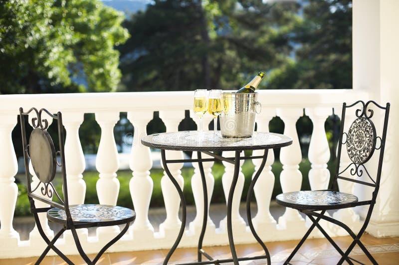 Champagneflaska och fyra flöjter på tabellen royaltyfria bilder