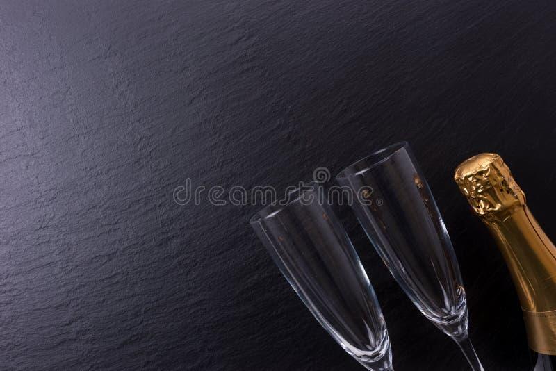 Champagneflaskan och två champagneexponeringsglas på svart kritiserar plattan royaltyfri foto
