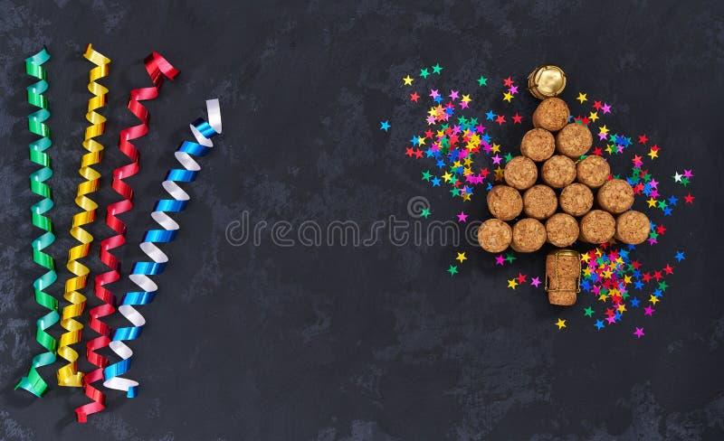 Champagnekorkar formade julträdet med konfettier på en svart bakgrund arkivfoton
