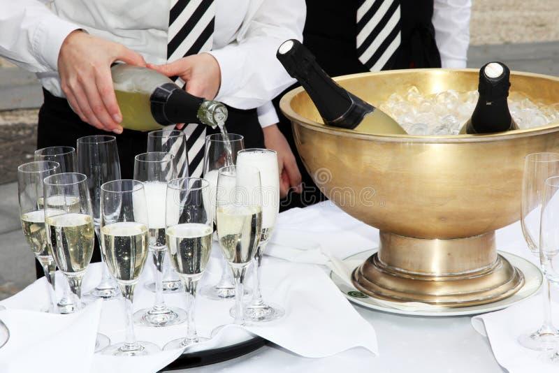champagnepåfyllningsexponeringsglas två uppassare royaltyfria foton