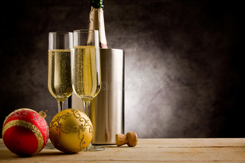 Champagner with Christmas Balls. Champagner Glasses on wooden table with christmas ornaments royalty free stock image